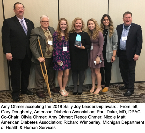 Amy Ohmer accepting the 2018 Sally Joy Leadership Award with (from left) Gary Dougherty, American Diabetes Association; Paul Dake, MD, DPAC Co-Chair; Olivia Ohmer; Amy Ohmer; Reece Ohmer; Nicole Matti, American Diabetes Association; Richard Wimberley, Michigan Department of Health & Human Services